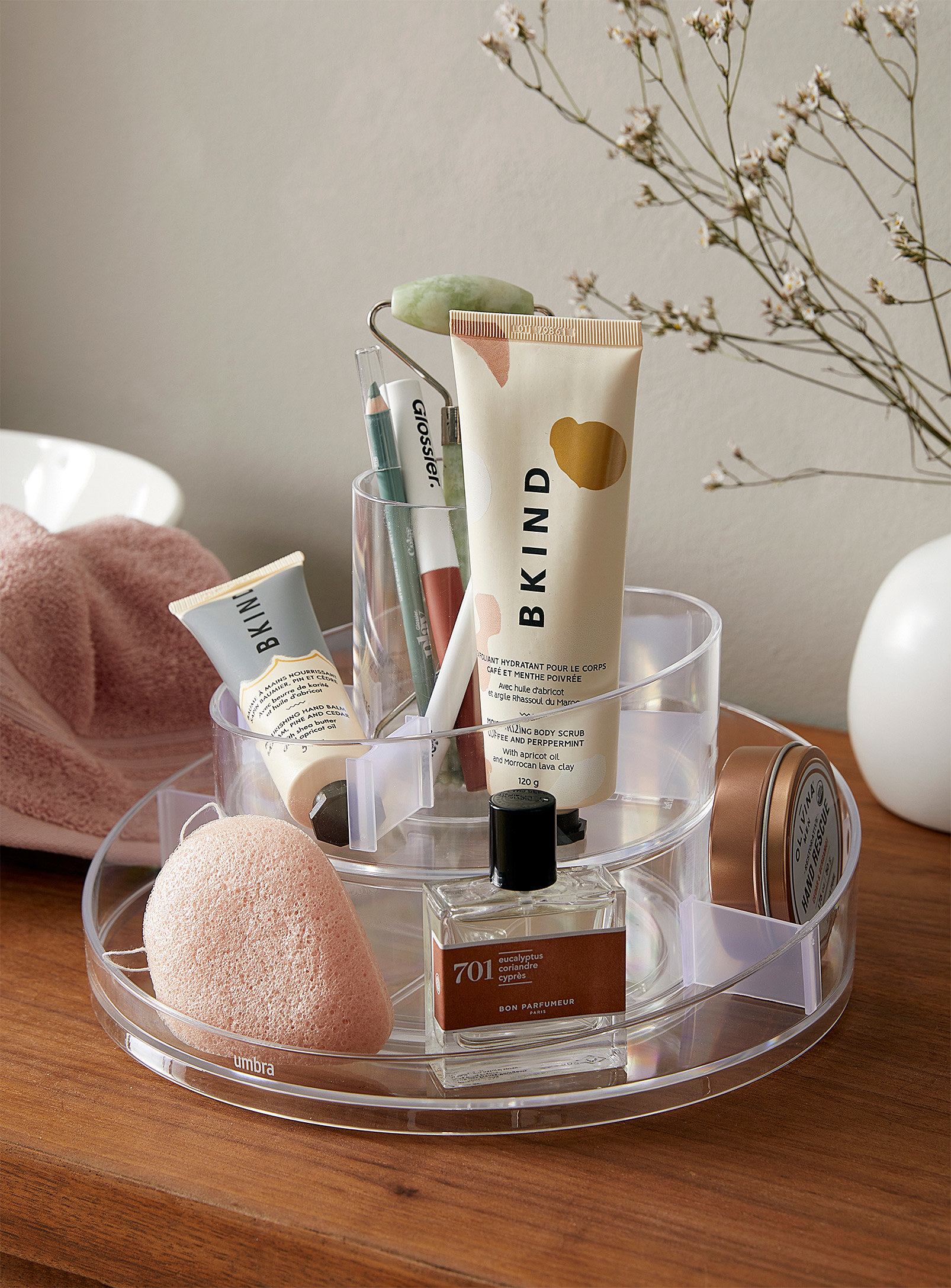 A round cosmetic organizer that's filled with small makeup and skincare products