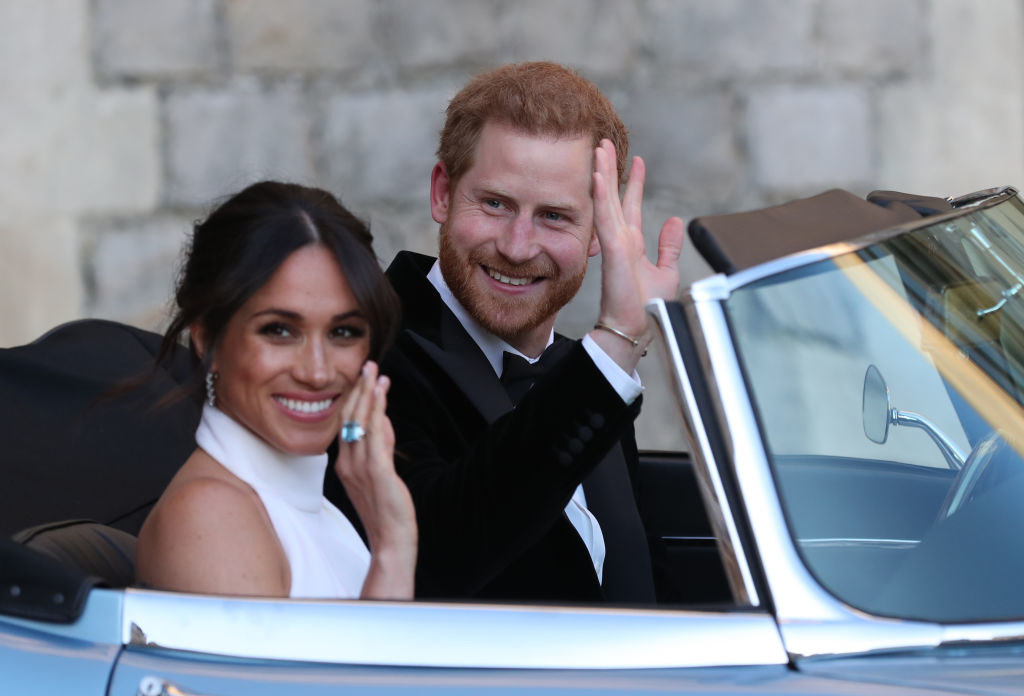 Meghan and Harry waving to the crowd as they drive away on their wedding day