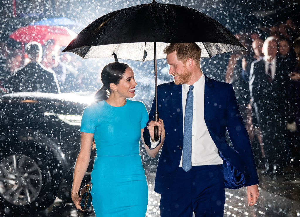 Meghan and Harry smiling at each other as they walk under an umbrella to an event
