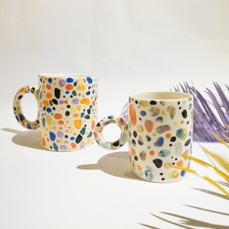 The cream mug with multi-colored speckles and a circle handle