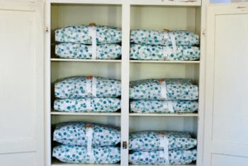 Cupboard with sheets wrapped in Bundle Buddy covers