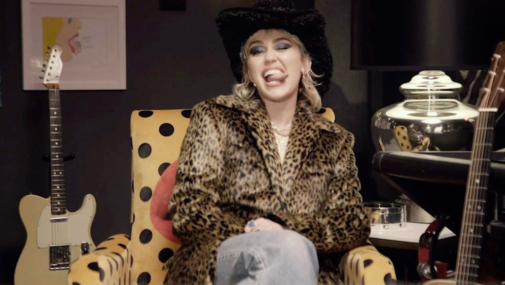 Miley sitting in a chair, wearing a leopard print coat and jeans, and sticking her tongue out