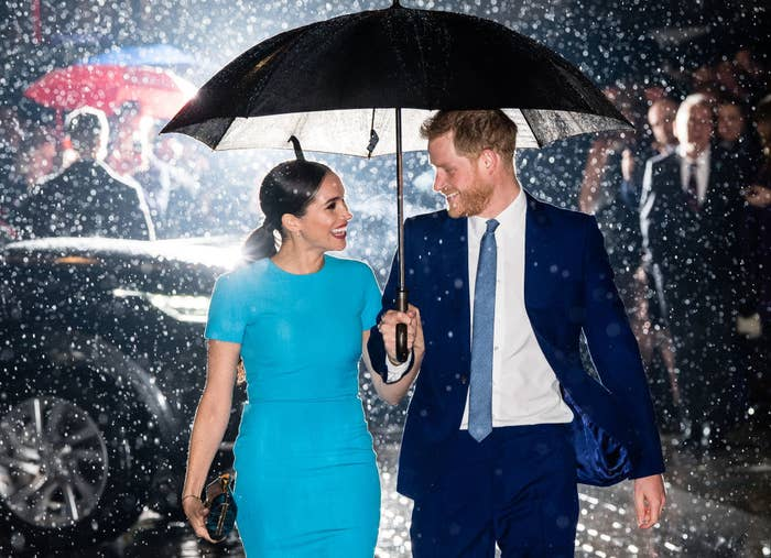 Harry and Meghan smiling at each other as they walk through the rain and hold an umbrella together