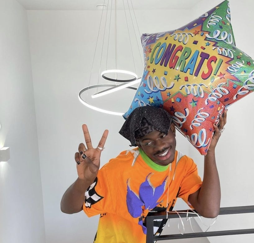 Lil Nas X poses with a balloon that says congrats!