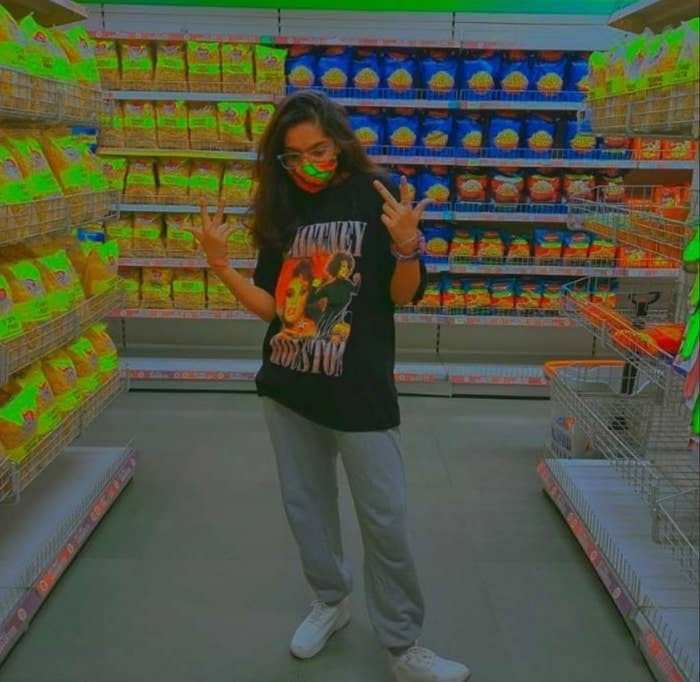 A high contrast image of my sister at the supermarket wearing a Whitney Houston t-shirt, grey joggers, white chunky shoes.
