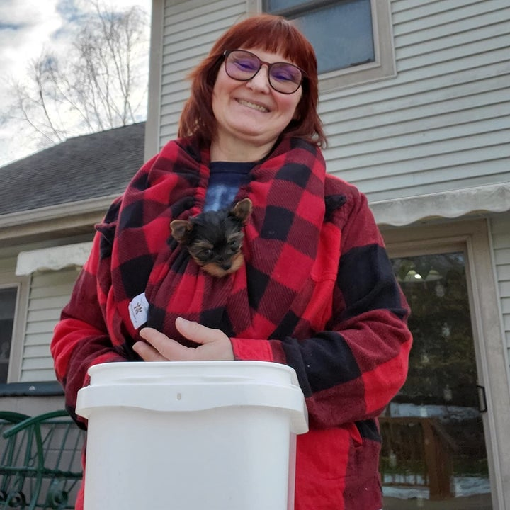 reviewer wearing the red and black plaid version to hold a yorkie puppy around their neck
