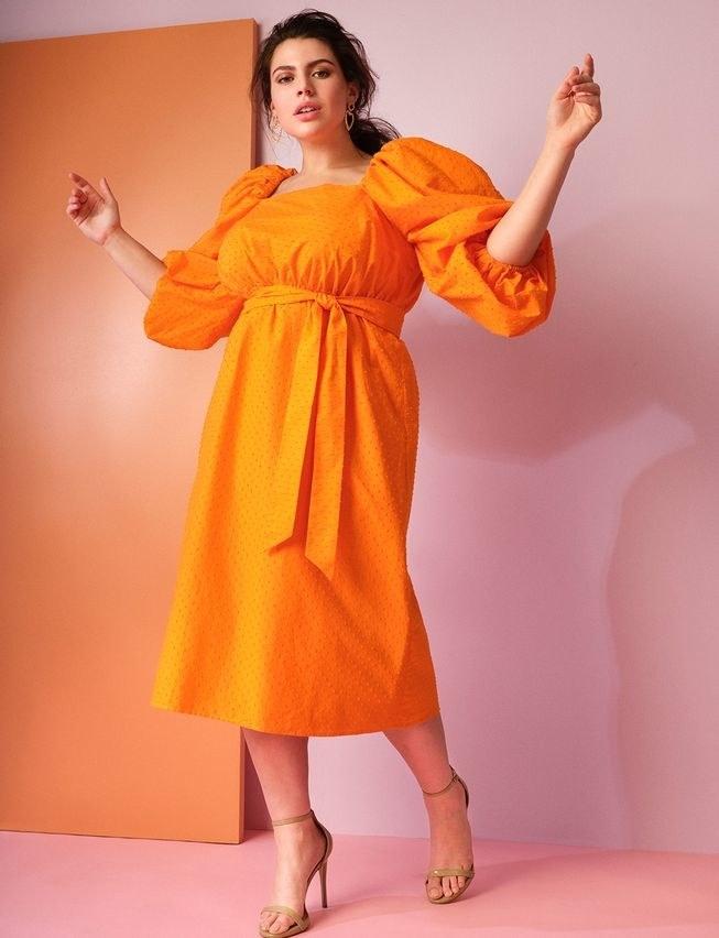 model wearing the mid calf-length puff-sleeve tie-waist dress in bright orange