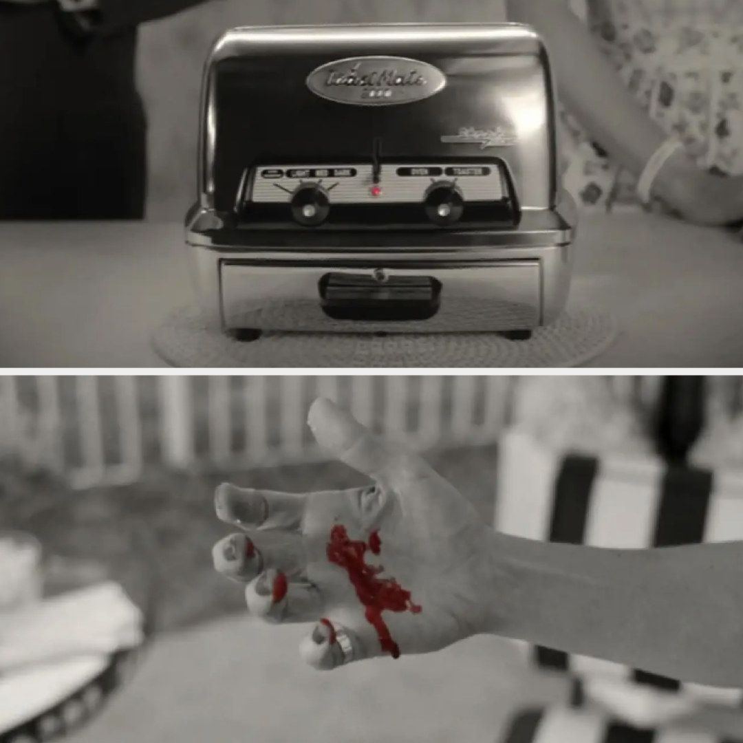 Black and white toaster with red blinking light and black and white hand with red blood