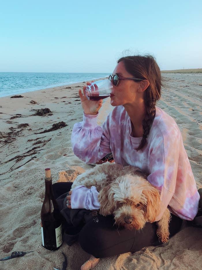 Me drinking wine on the beach with my sleepy dog.