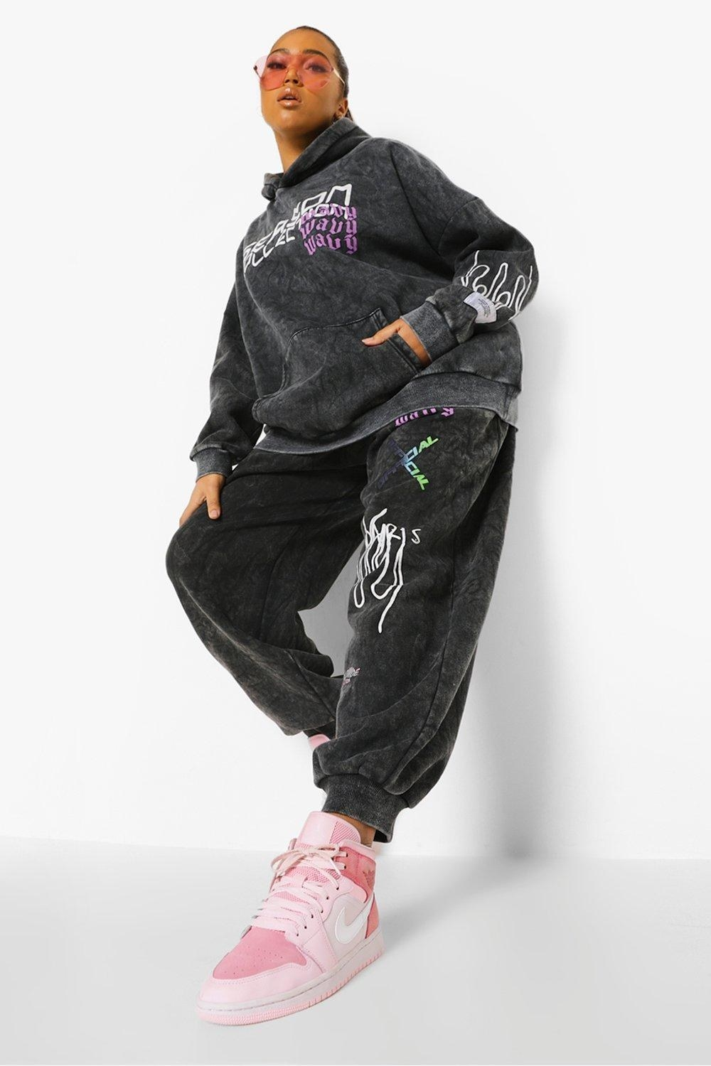 model wearing matching grey sweatshirt and sweatpants with illustrations on both