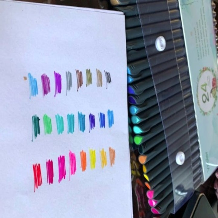 pack of colored pens with sample scribbles on a notebook page