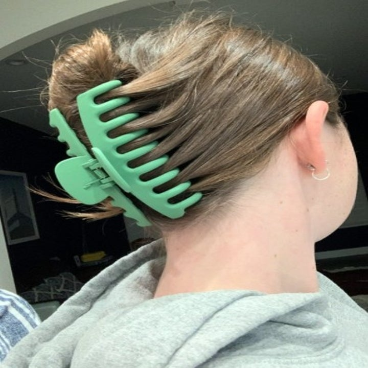 a green claw clip holding up a person's hair