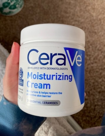 person holding up a large tub of cerave cream