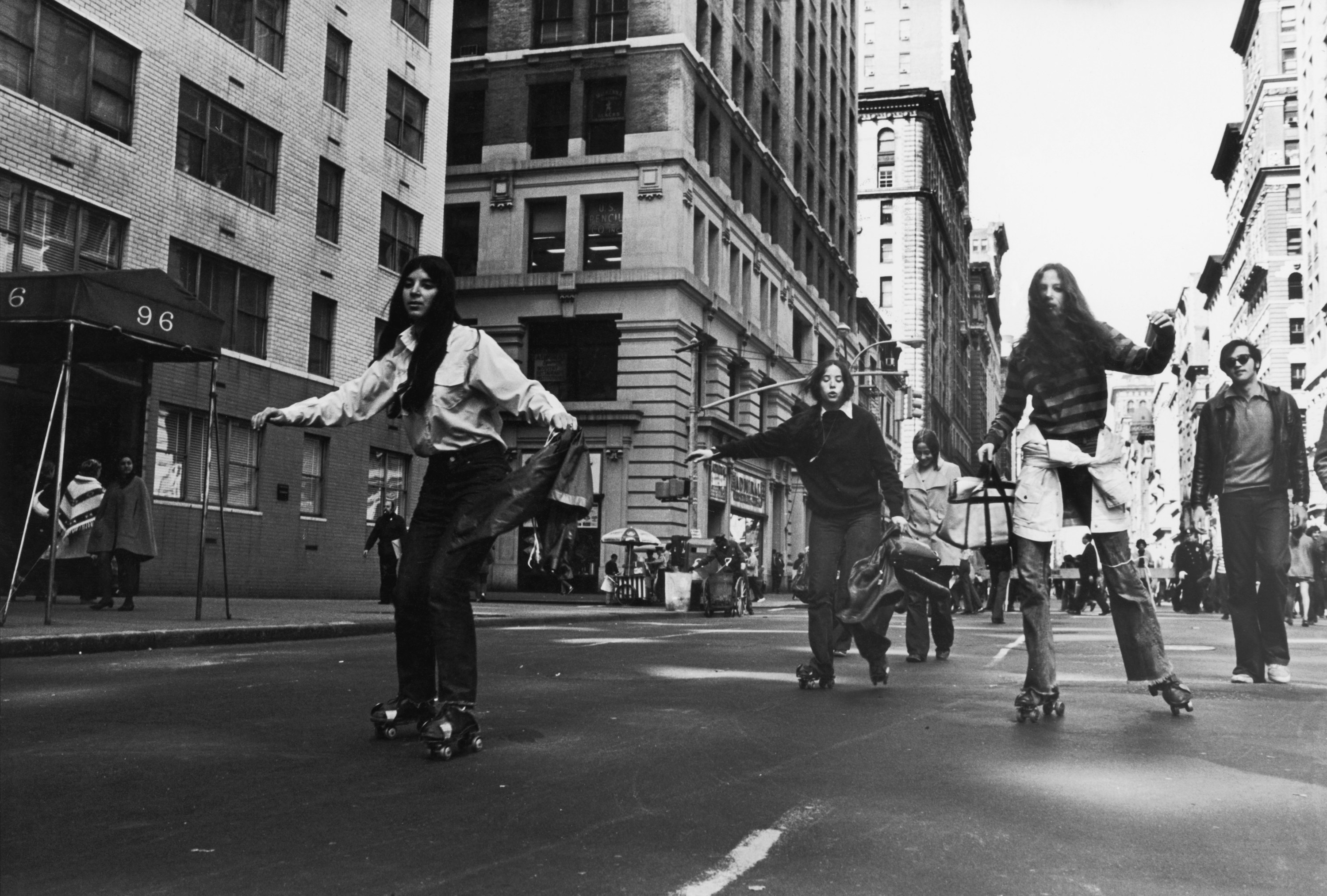 A group of people roller-skate down an empty street in 1970