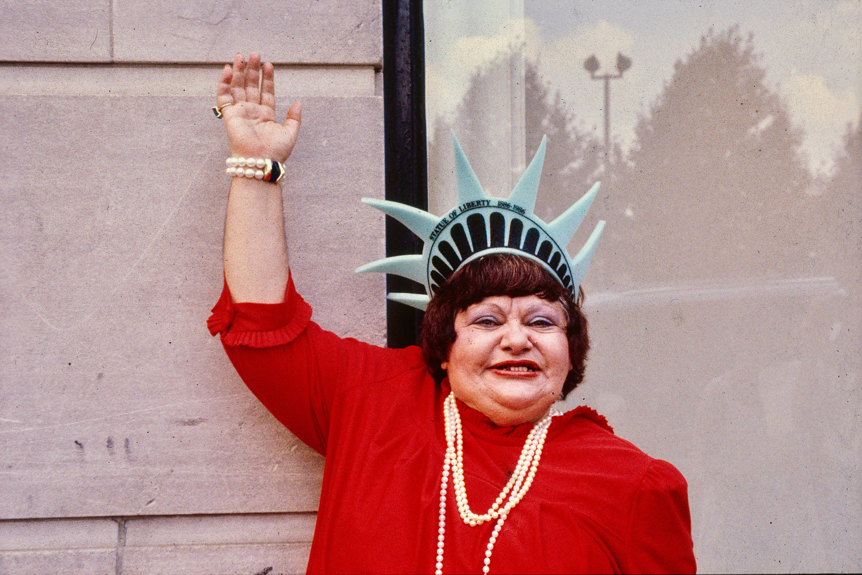A woman wearing a foam Statue of Liberty novelty visor and a pearl necklace waves to the camera