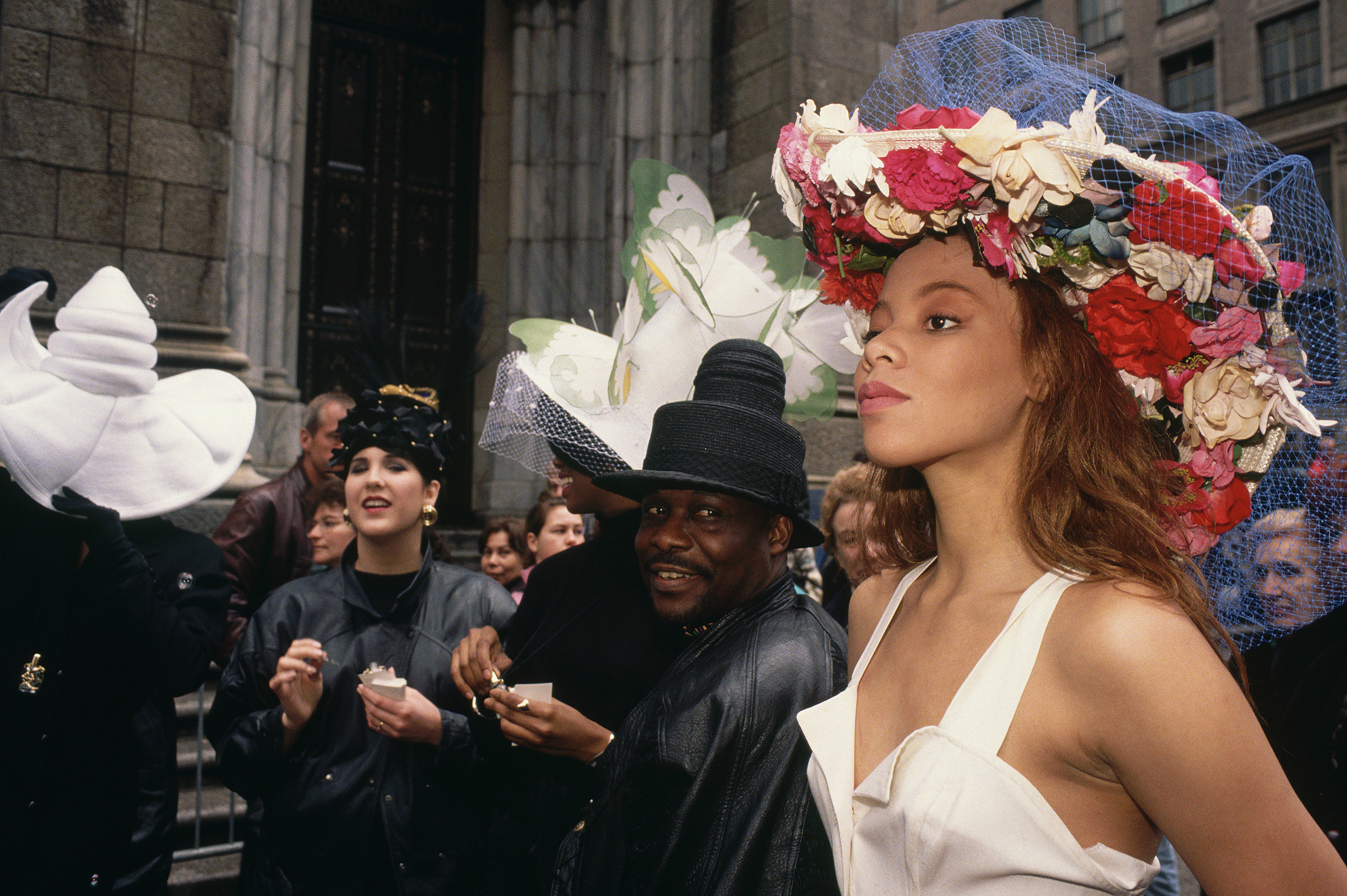 A woman in a floral hat outside a church and men in black