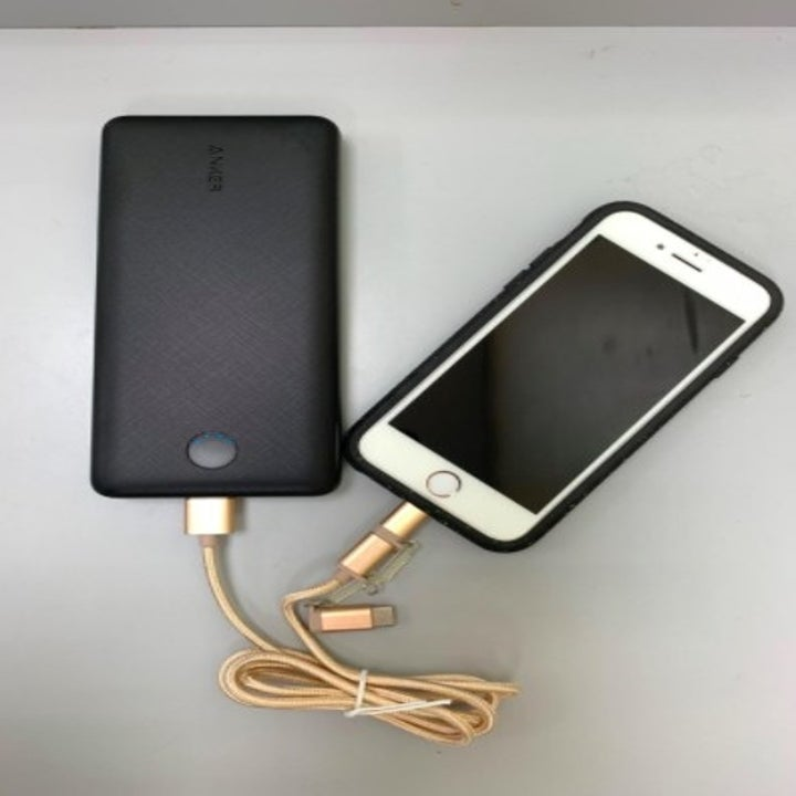 black portable charger charging an iphone through a gold cord