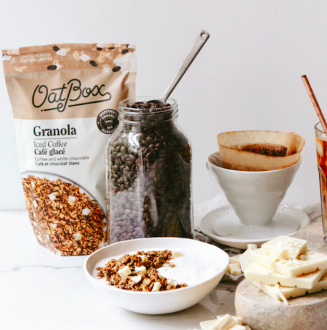 A bag of coffee-flavoured granola next to a bowl of yogurt and a jar of coffee beans