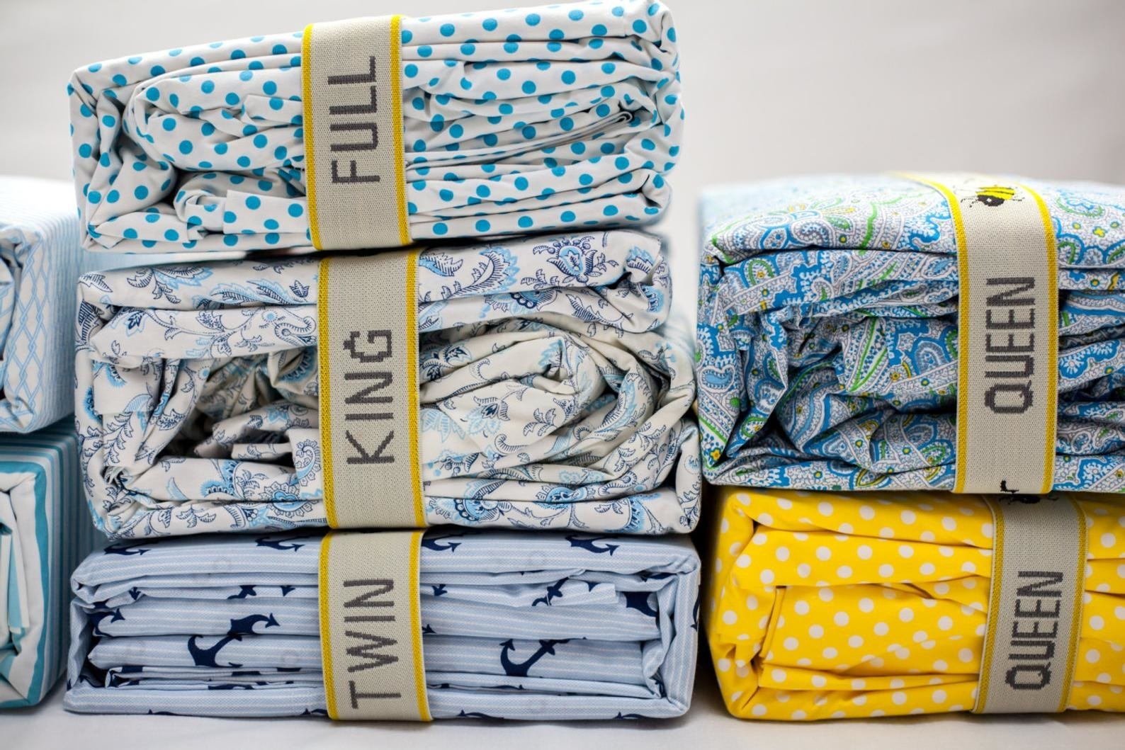 stacks of sheets with yellow and off white bands wrapped around them to keep them orderly