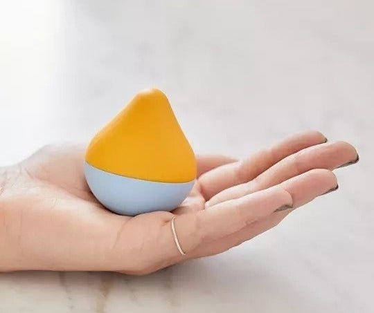 Teardrop shaped toy that fits in the palm of the model's hand