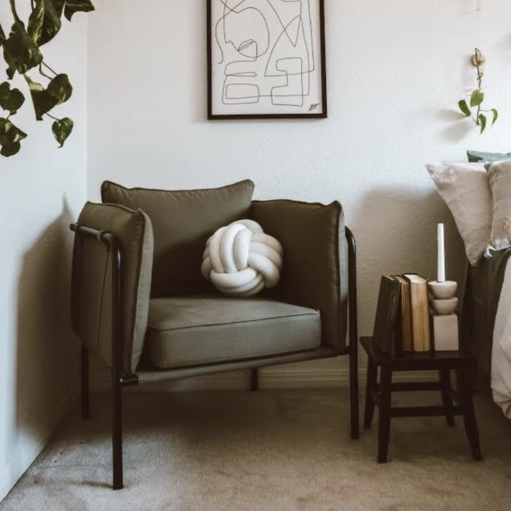 a white knot pillow on a green accent chair