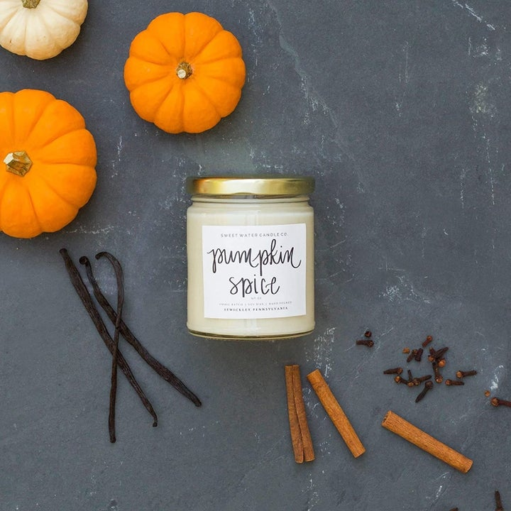 pumpkin spice candle in clear glass jar surrounded by spices and small pumpkin