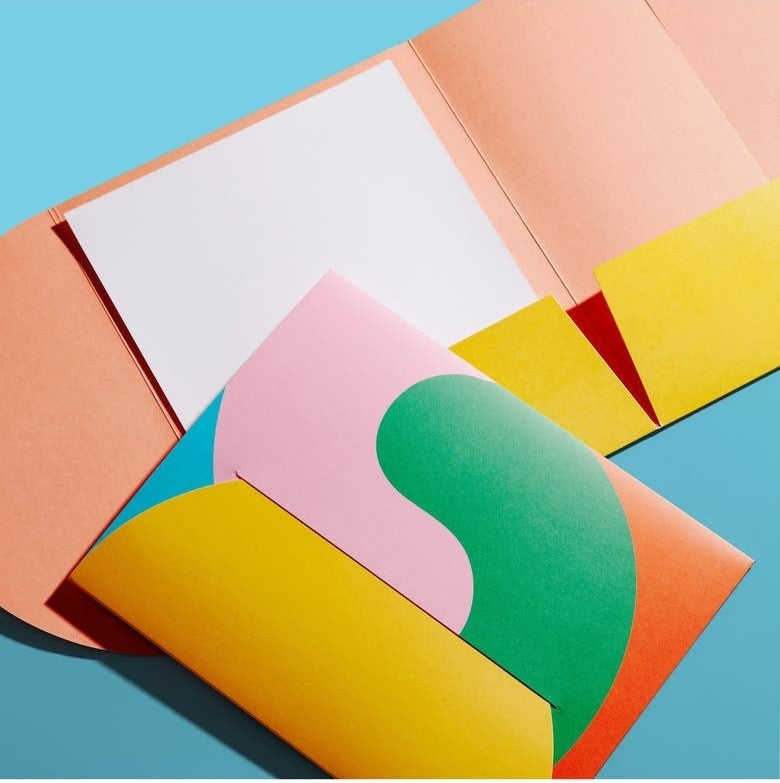 two-pocket folder with rounded edge that folds into the front to close, in brightly colored yellow, pink, green, blue, and orange, swirly pattern