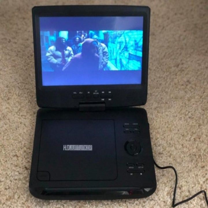 a portable dvd player playing a movie while sitting on the floor