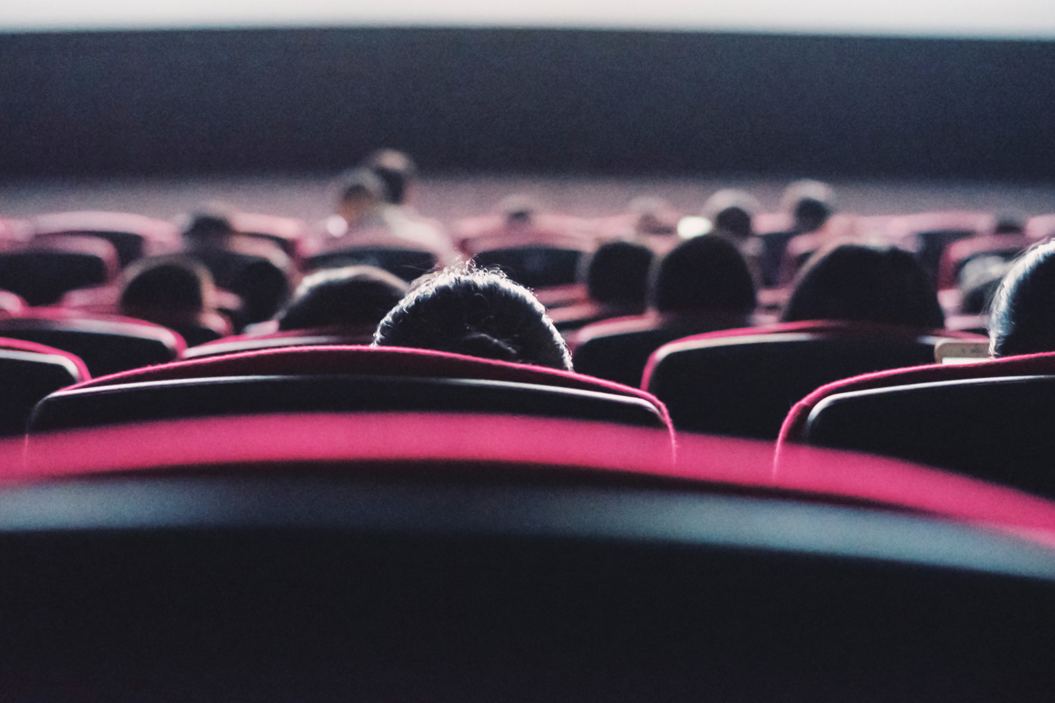 A view of the backs of movie theater seats with people sitting in them