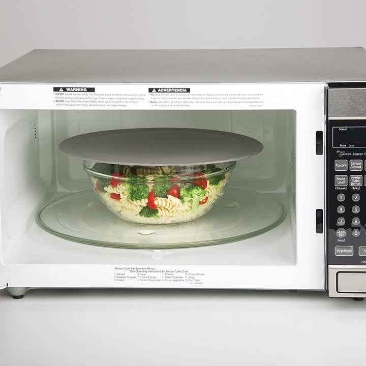 multi purpose mat being used as a splatter guard on top of a dish that's being microwaved