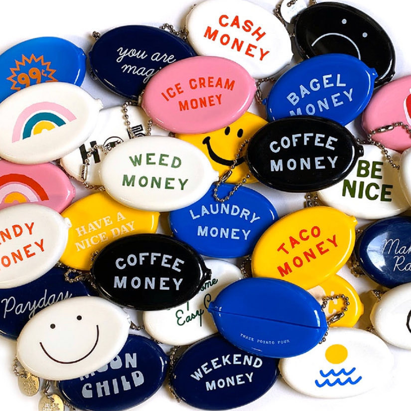 a pile of different rubbery coin pouch keychains with different phrases on them