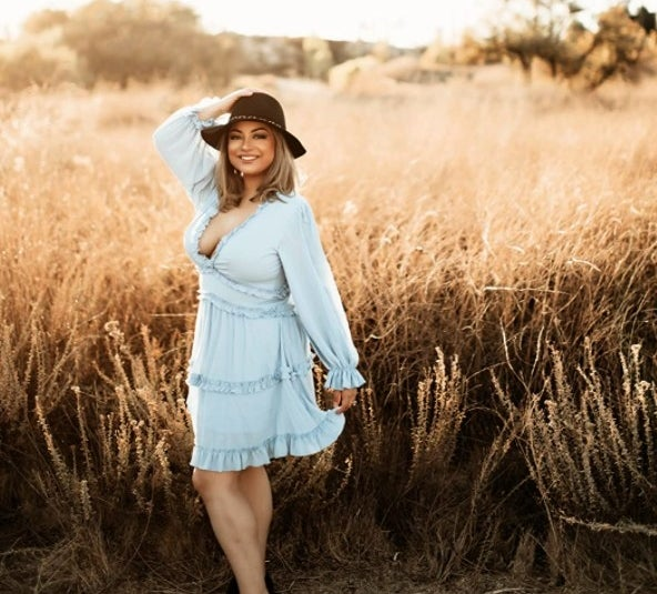 A reviewer wearing the dress in baby blue standing in a field