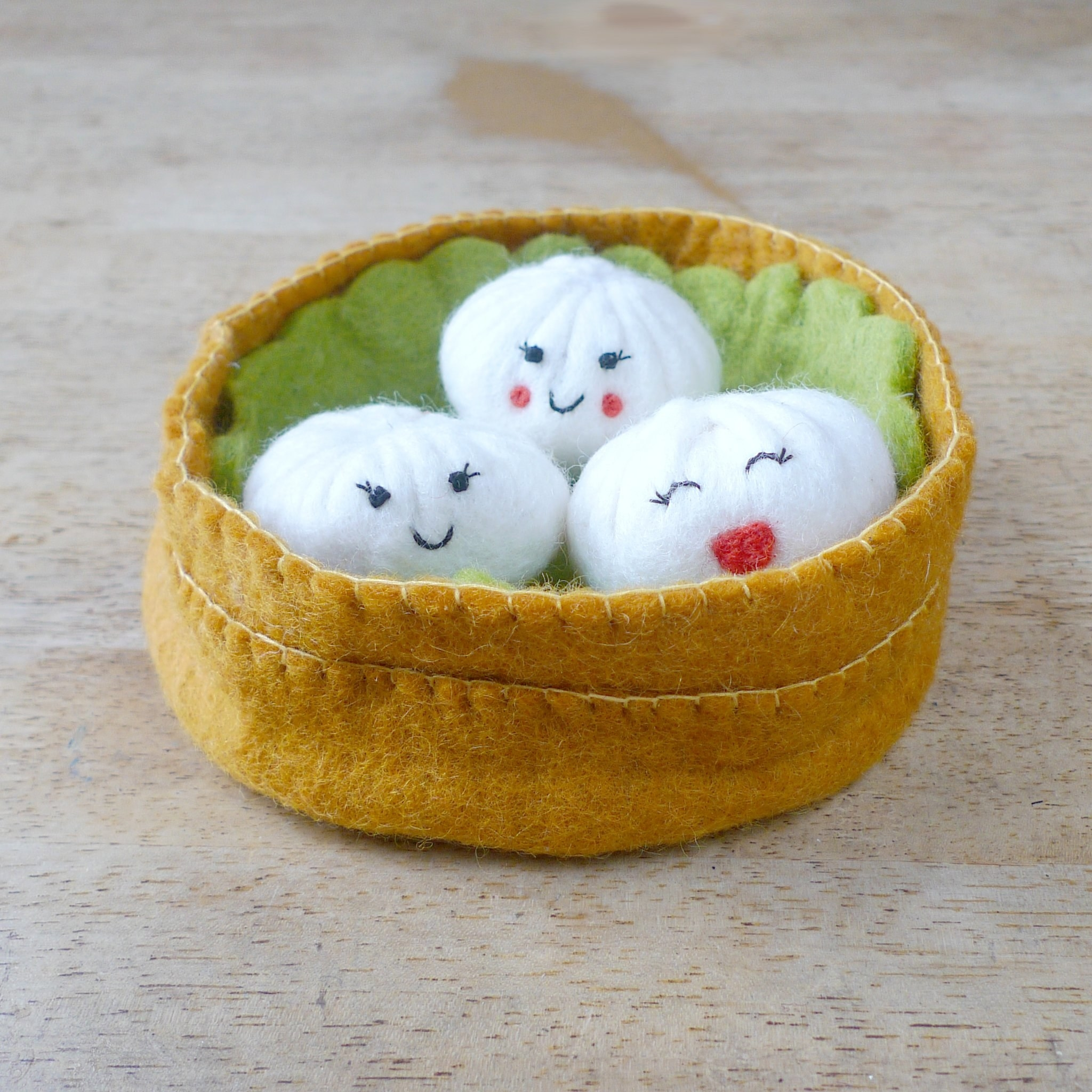 The toy that looks like like three soup (with cute smiling faces) dumplings in a steamer