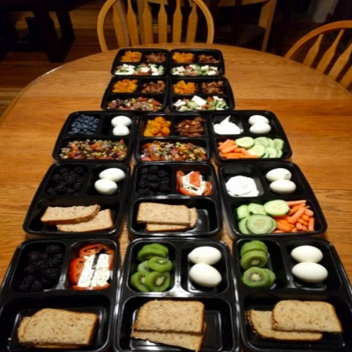 lots of black food storage containers laid out with various food stashed in each compartment