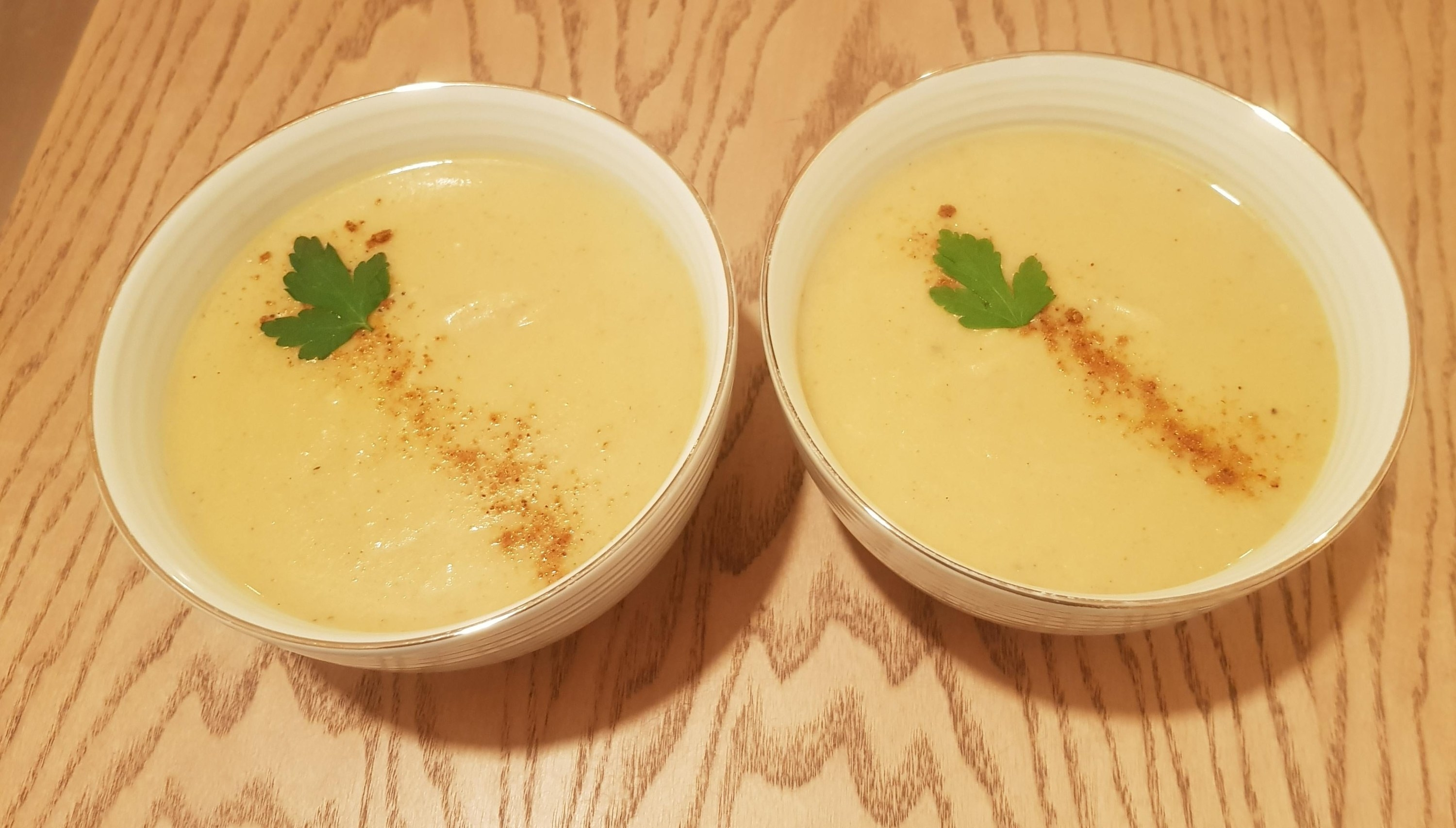 Two bowls of curry creamy cauliflower soup.