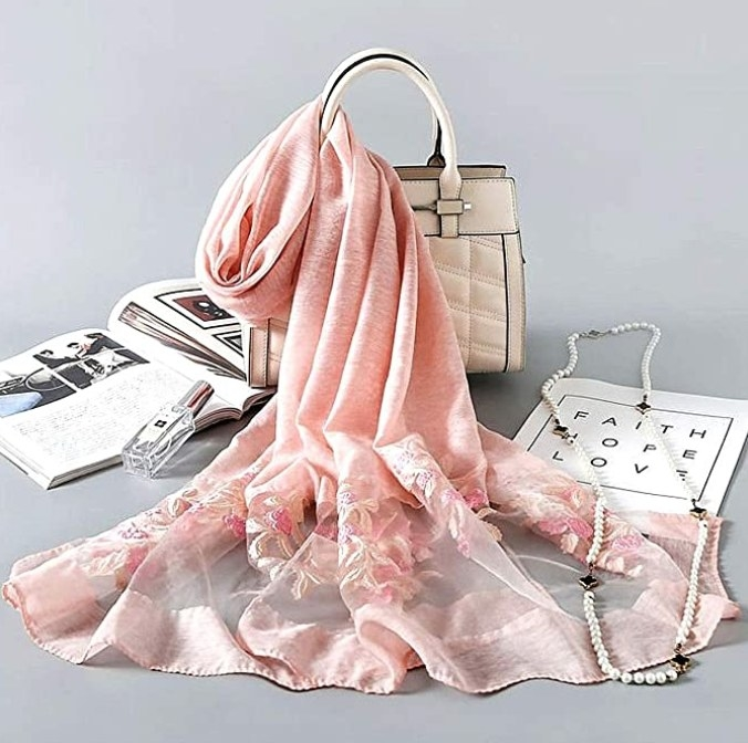 The scarf in pink tied around a purse