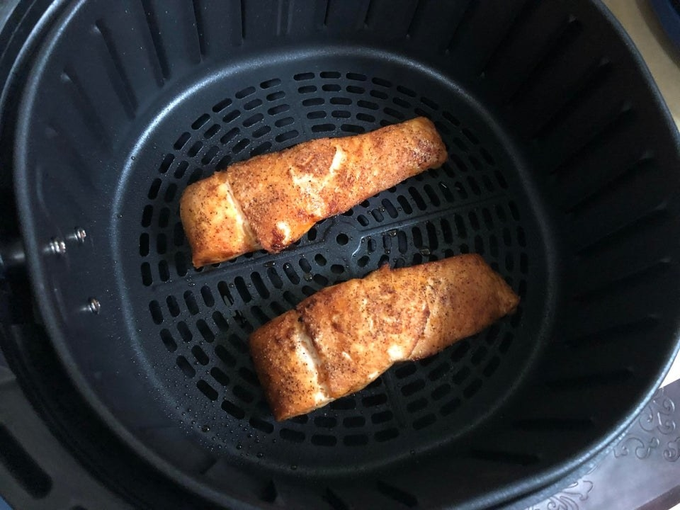 Crispy salmon in the basked of an air fryer.