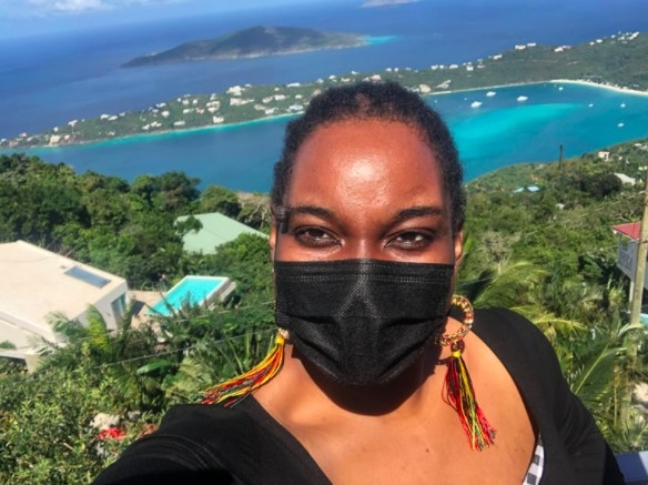 person wearing a black face mask with a tropical background behind her