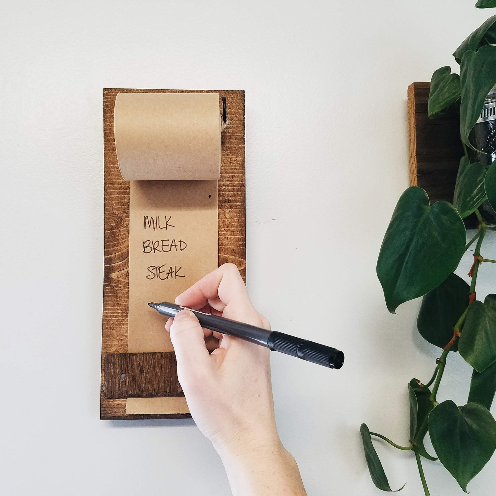 wood panel on a wall with a roll of brown paper being held down and a hand writing different food on it