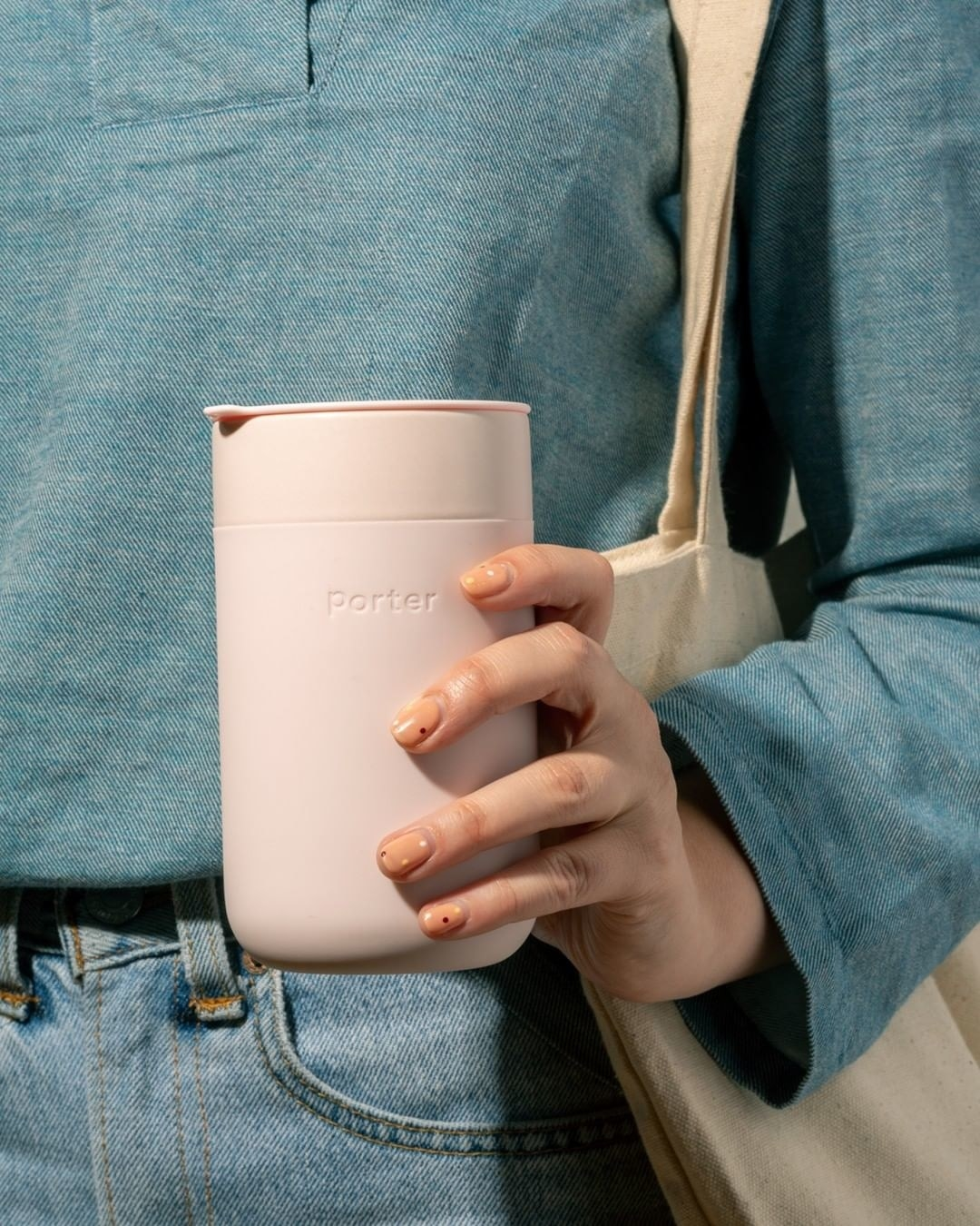 A person holding the tumbler in front of them