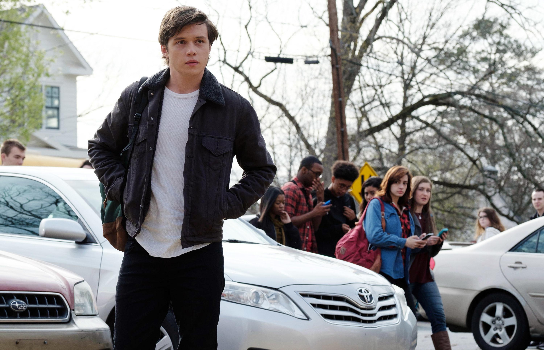 simon near cars outside school with classmates behind him