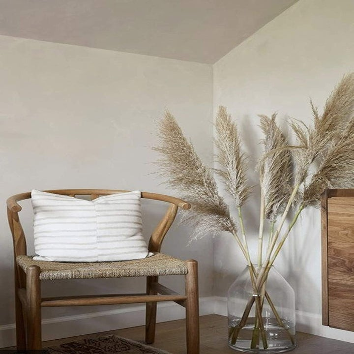 same dried pampas grass in a tall clear vase next to an arm chair