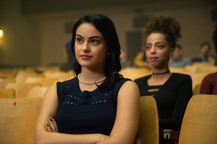 Camila Mendes sits in an auditorium with her arms crossed in Riverdale