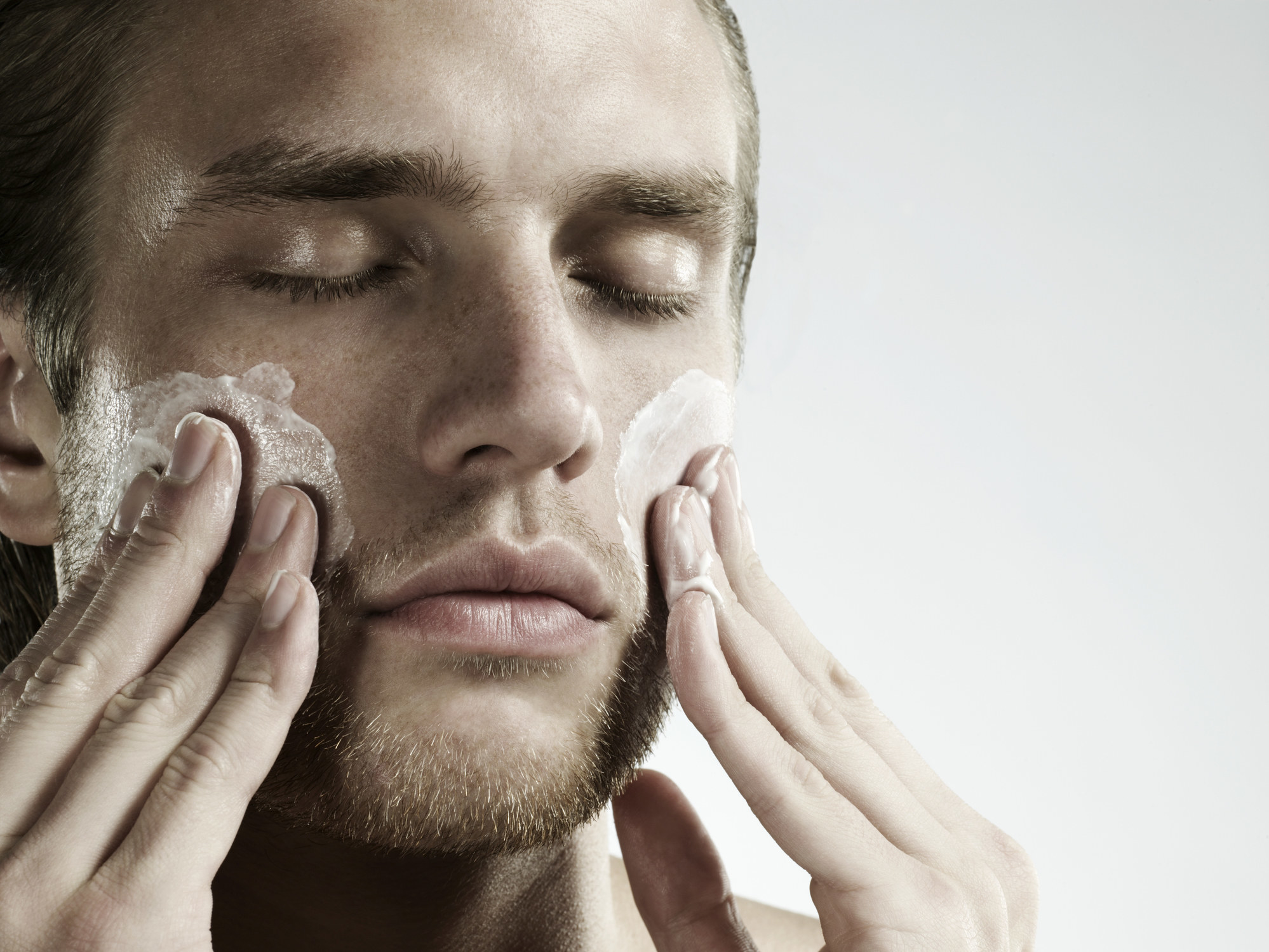 Man putting on moisturizer
