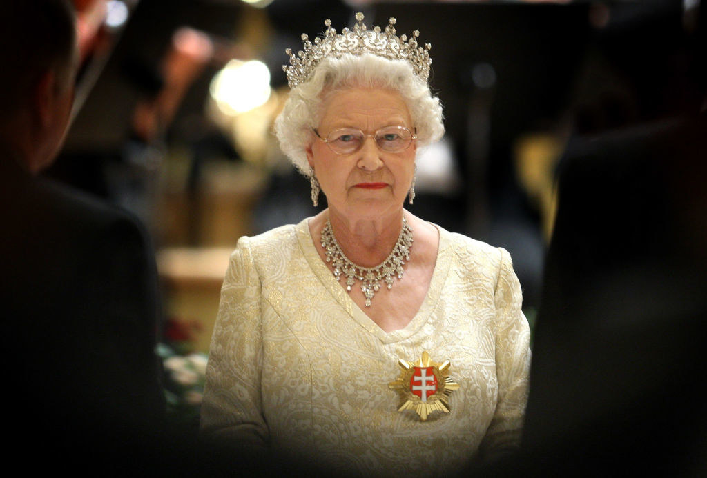 The Queen wearing a crown, matching diamond necklace, and a gown at a formal event
