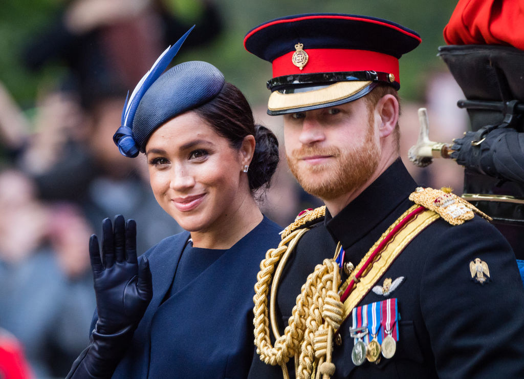 Prince Harry, wearing his military uniform, and Meghan sit in a carriage during a formal event