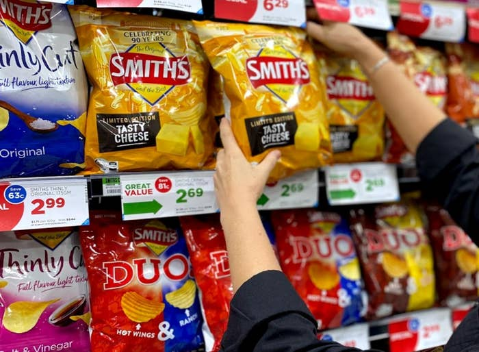 """Hands reaching for a packet of """"Tasty Cheese"""" Smith's chips on the shelf amongst other Smith's flavours"""