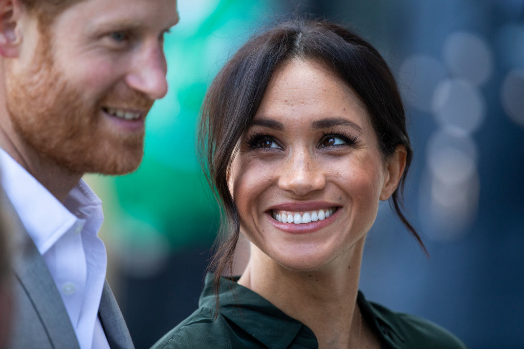 Meghan smiling widely at Harry