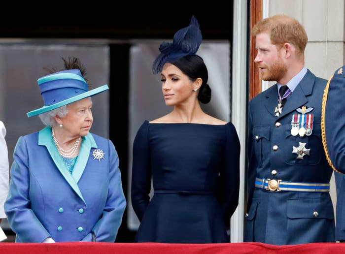 The Queen, Meghan, and Harry standing on a balcony during a events