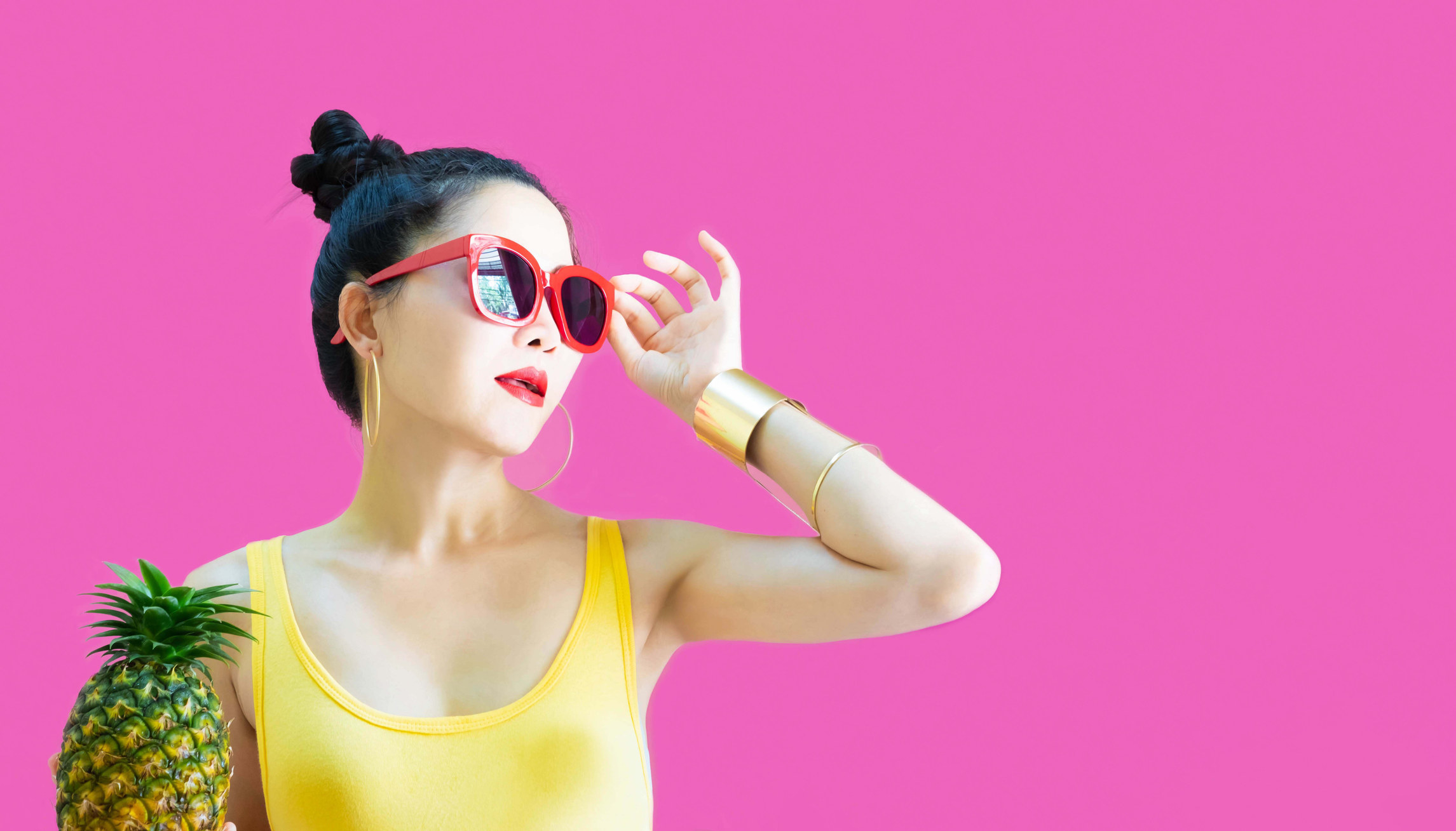 Woman holding a pineapple while wearing red sunglasses